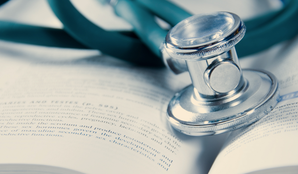 Health care compliance image for Kaplan Health Innovations, includes stethoscope and medical book